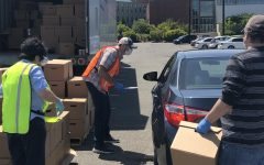 VOA Director of Marketing and Communications, Cory Armstrong-Hoss (Middle) speaking with someone as volunteers load boxes of food into their trunk at the drive-through food bank distribution site in parking lot J of EvCC's main campus on Wednesday, Jun. 3 to help stop food insecurity around Snohomish County.