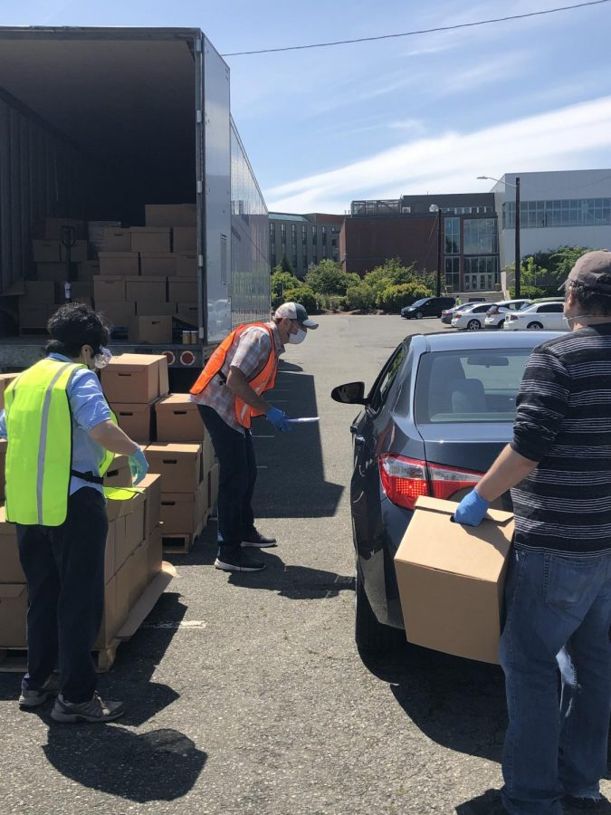VOA+Director+of+Marketing+and+Communications%2C+Cory+Armstrong-Hoss+%28Middle%29+speaking+with+someone+as+volunteers+load+boxes+of+food+into+their+trunk+at+the+drive-through+food+bank+distribution+site+in+parking+lot+J+of+EvCC%E2%80%99s+main+campus+on+Wednesday%2C+Jun.+3+to+help+stop+food+insecurity+around+Snohomish+County.