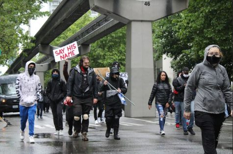 Black Lives Matter protesters marching down the streets of downtown Seattle on May 30, 2020. One of them holds a sign that says
