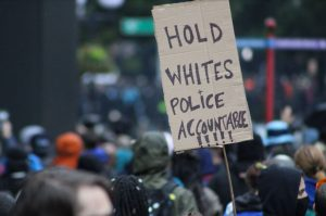 Black Lives Matter protester holds a sign saying