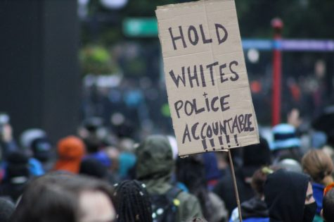 "Black Lives Matter protester holds a sign saying ""hold whites and police accountable"", on May 30, 2020."