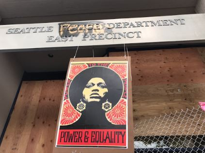 "The abandoned Seattle Police Department East Precinct on Capitol Hill, defaced as the ""Seattle People Department East Precinct"" decorated with a sign that reads ""Power & Equality""."