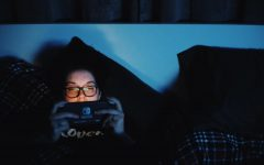 Leeanna Digruccio, an EvCC Student, is playing games on her Nintendo Switch in a darkly lit room.