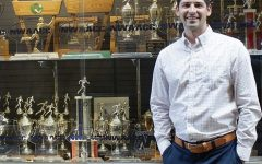 Garet Studer, EvCC's Athletic Director, poses in front of the fitness center's trophy case.