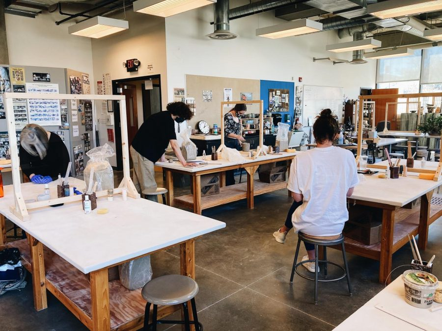 """Fewer students, masks required, plexiglass partitions and hand sanitizer on each table are just a few of the COVID-19 safety protocols in place. Sam Weiland (center), """"I feel safe with everything that"""
