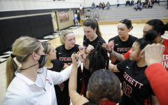 Coach Cheryl Sorenson (white) in a pre-game huddle before tip off of the first game of the season at Peninsula CC on April 3, 2021. EvCC won 48-43.